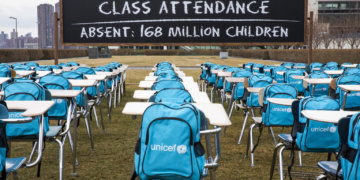 "On 1 March 2021, a view of UNICEF's 'Pandemic Classroom' installation at United Nations Headquarters in New York, United States of America.  To call attention to the education emergency wrought by the COVID-19 pandemic, and to and raise awareness of the need for governments to keep schools open, UNICEF unveiled 'Pandemic Classroom' – a model classroom made up of 168 empty desks, each seat representing one million children living in countries where schools have been almost entirely closed since the onset of lockdowns. ""With every day that goes by, children unable to access in-person schooling fall further and further behind, with the most marginalized paying the heaviest price,"" said UNICEF Executive Director Henrietta Fore. ""No effort should be spared to keep schools open, or prioritise them in reopening plans."" On the installation, Fore added, ""Behind each empty chair hangs an empty backpack – a placeholder for a child's deferred potential … We do not want shuttered doors and closed buildings to obscure the fact that our children's futures are being put on indefinite pause."" School closures have devastating consequences for children's learning and wellbeing. The majority of schoolchildren worldwide rely on their schools as a place where they can interact with their peers, seek support, access health and immunization services and a nutritious meal. The longer schools remain closed, the longer children are cut off from these critical elements of childhood.   According to new data released today by UNICEF, schools for more than 168 million children globally have been completely closed for almost an entire year due to COVID-19 lockdowns. Furthermore, around 214 million children globally – or 1 in 7 – have missed more than three-quarters of their in-person learning. As students return to their classrooms, they will need support to readjust and catch up on their learning. UNICEF urges governments to prioritise every student's uniqu"